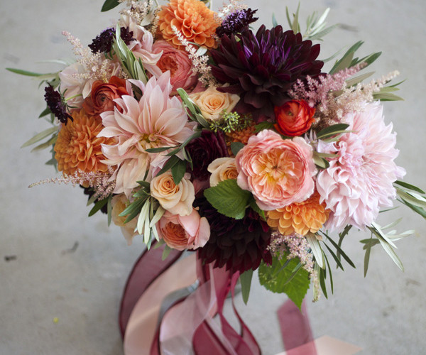 Bridal bouquet by Bella Fiori, wedding at Maplehurst Farms in Mt Vernon, Washington. Bouquet with burgundy dahlias, peach garden roses, peach ranunculus, orange dahlias