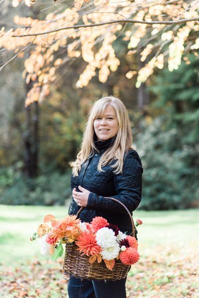 Alicia Schwede of Bella Fiori holding an arrangement of dahlias from the garden.